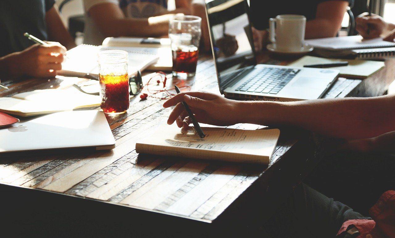 デスク上のノートとペンとパソコン