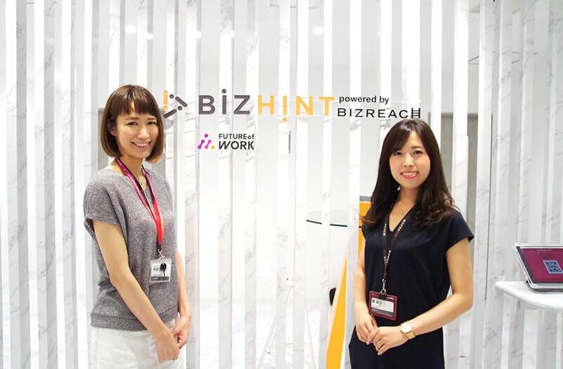 写真: オフィスエントランスに立つ2名の女性