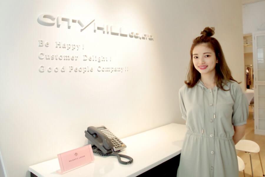 写真: オフィスエントランスに立つ若い女性