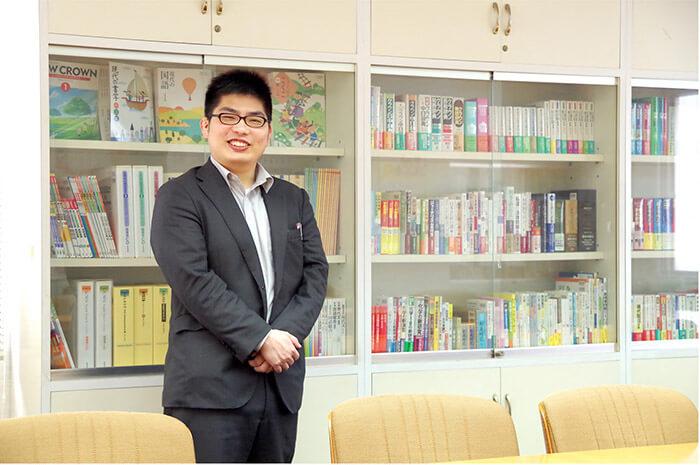 写真: 本棚の前に立つスーツ姿の男性
